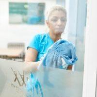 Frau reinigt mit Tuch Glas